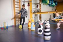 Poika kuljettaa keltaista palloa liikuntasalissa