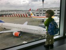 Pieni poika katsoo lentokentällä ikkunasta lentokoneita.