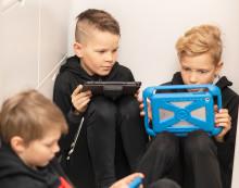 Pojat tutkivat tablettitietokoneitaan