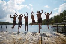 Pojat hyppäämässä laiturillta järveen uimarannalla