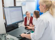 Sairaanhoitaja kirjoittaa tietokoneella potilaan tietoja.