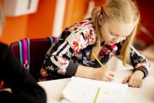 Saparopäinen tyttö kirjoittaa pulpetin ääressä / Hanna-Kaisa Hämäläinen