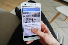 Kädessä älypuhelin, jossa auki Jyväskylän kaupungin verkkosivut