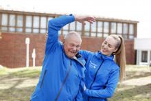 Seniorimies ja liikunnanohjaaja ulkona venyttelemässä