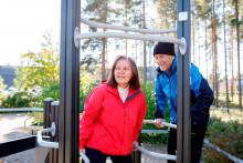 Kaksi senioria kuntoilee ulkona liikuntapuistossa