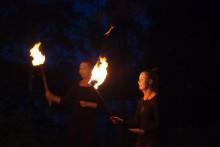 Ulkona pimeässä kaksi naista kädessään tulisoihdut