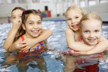 Neljä tyttöä AaltoAlvarin uima-altaassa toistensa reppuselässä