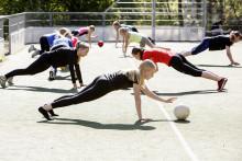 Tytöt liikuntatunnilla pallojen avulla jumppaamassa