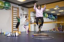 Tyttö hyppää korkealle ilmaan liikuntasalissa