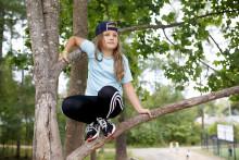 Tyttö istuu puunoksalla