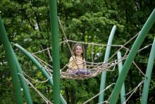 Tyttö istuu kiipeilyverkon päällä.