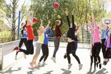 Urheiluluokan tytöt pelaavat palloilla ulkokentällä