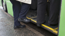 Avustaja auttaa asiakkaan linja-autoon