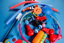 Värikkäitä liikuntavälineitä kasassa lattialla