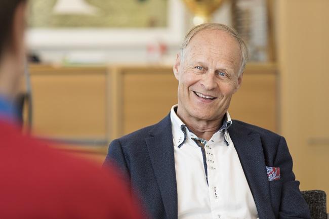 Kiinteistöjohtaja Esko Eriksson haastateltavana pöydän ääressä