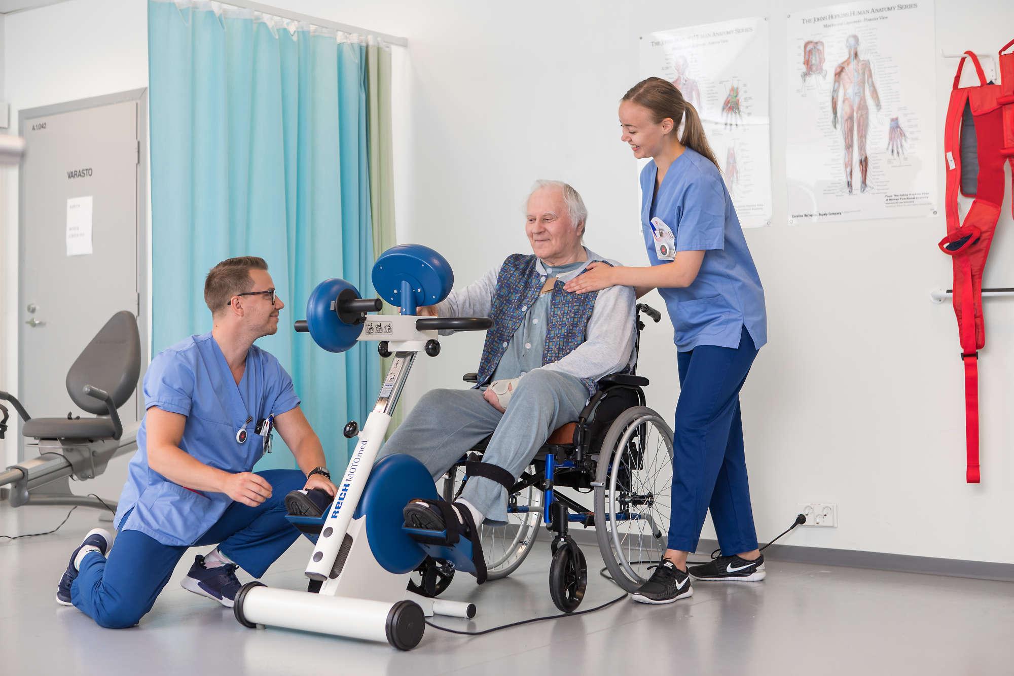 Fysioterapeutit avustavat asiakasta osaston kuntosalilla.
