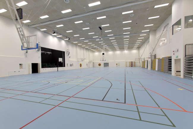 Huhtasuon yhtenäiskoulun liikuntasalin siniseen lattiaan on maalattu eri pelien rajoja