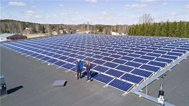 Kiinteistönhoitaja Petri Niutanen ja energia-asiantuntija Tero Hirvelä seisovat aurinkopaneelien edessä