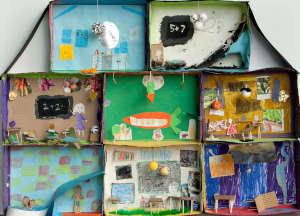 Puistokoulun 2A ja 2B -luokkien taideteos, missä askarreltuna erilaisia luokkahuoneita