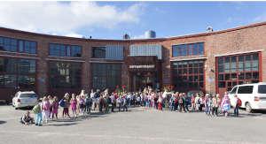 Iso joukko toppuluokkalaisia Veturitallien edessä odottamassa Tilapalvelun 20-vuotisjuhlan aloitusta