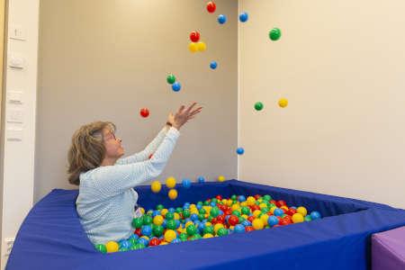 Pedagoginen johtaja Sara Volotinen heittää palloja ilmaan pallomeressä istuen